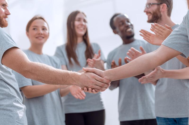 grupa ludzi uśmiecha się do siebie, klaszcze i podaje sobie ręce